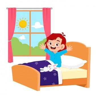 Feliz criança menina bonitinha acorda de manhã