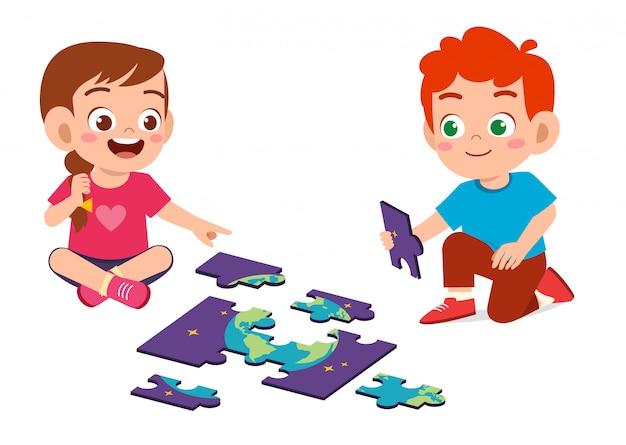 Feliz criança menino e menina jogar quebra-cabeça