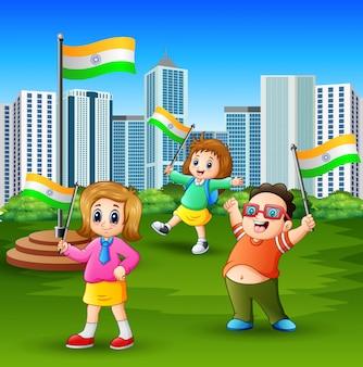Feliz crianças segurando a bandeira nacional no parque da cidade