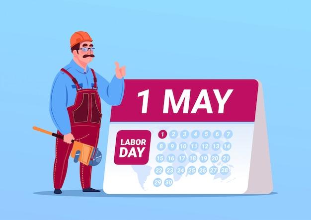 Feliz dia do trabalho de 1 de maio com construtor ou engenheiro sobre o calendário