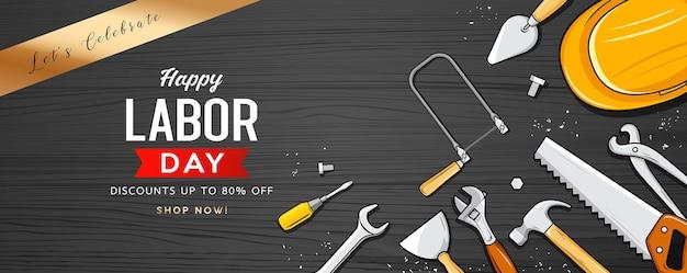 Feliz dia do trabalho vamos comemorar a venda ferramentas de construção design de banner em fundo preto de madeira