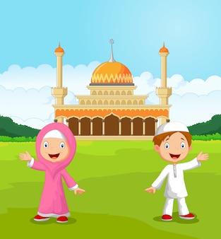 Feliz dos desenhos animados crianças muçulmanas acenando a mão na frente da mesquita