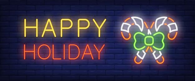 Feliz feriado neon texto e dois bastões de doces