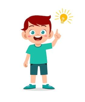 Feliz garoto menino bonitinho com sinal de lâmpada de ideia