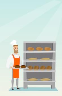 Feliz jovem padeiro segurando uma bandeja com pão.