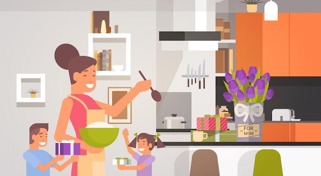 Feliz mãe sorridente com crianças na cozinha saudação dia das mães, férias de primavera