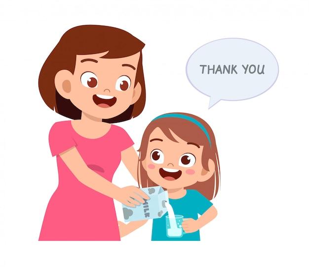 Feliz menina bonitinha beber leite com a mãe