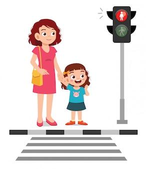 Feliz menina criança bonitinha atravessar a rua com a mãe