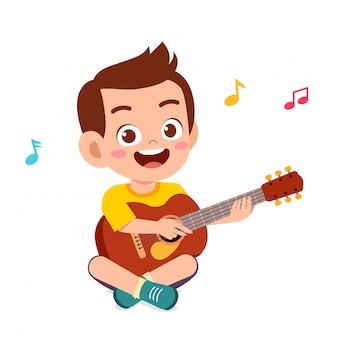 Feliz menino bonitinho tocar guitarra