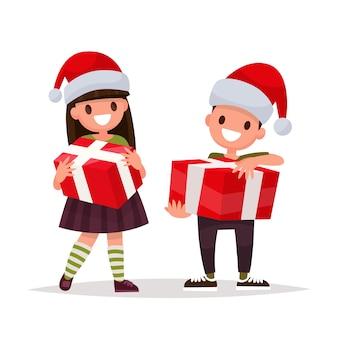 Feliz menino e menina com presentes de natal.