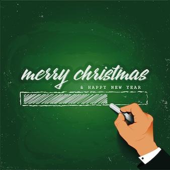 Feliz natal carregando mão escrevendo com giz em um quadro negro