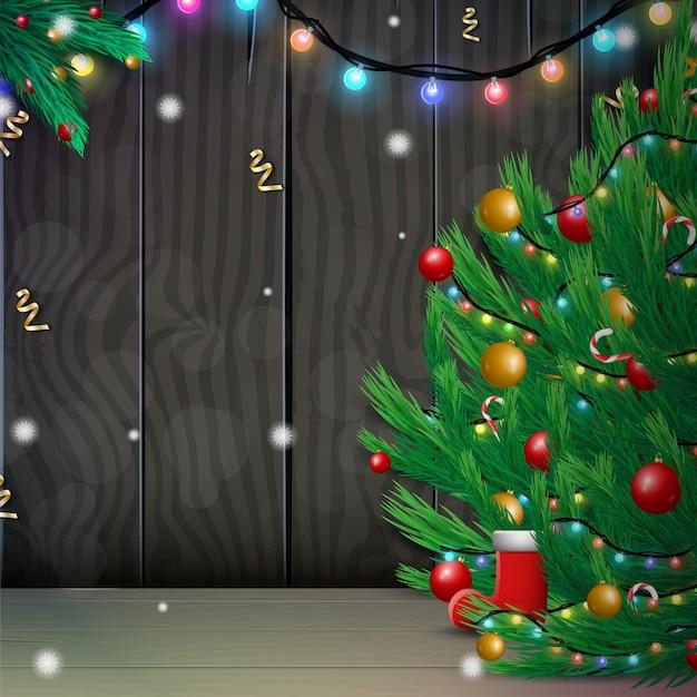 Feliz natal e feliz ano novo com árvore de natal decorada e guirlanda de luzes cintilantes em fundo madeira