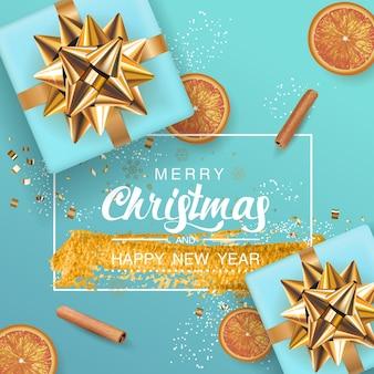 Feliz natal e feliz ano novo fundo azul com caixa de presente azul realista, frutas laranjas, pau de canela. letras de quadro com pincel respingo de tinta dourada.
