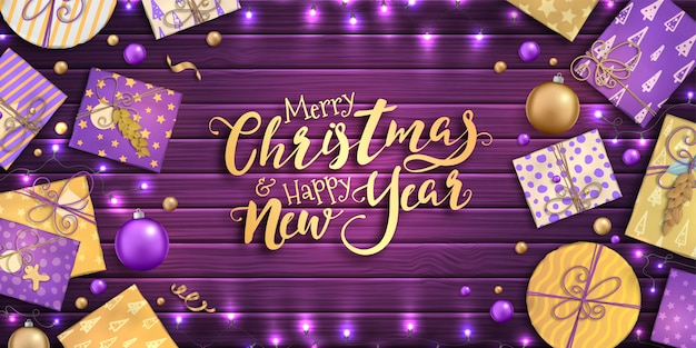 Feliz natal e feliz ano novo. fundo com decoração de natal - enfeites de roxos e dourados, caixas de presente de artesanato e guirlandas em pano de fundo de madeira