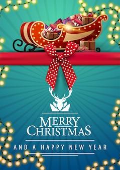 Feliz natal e feliz ano novo, postal vertical azul com fita horizontal vermelha com laço, guirlanda e trenó do papai noel com presentes