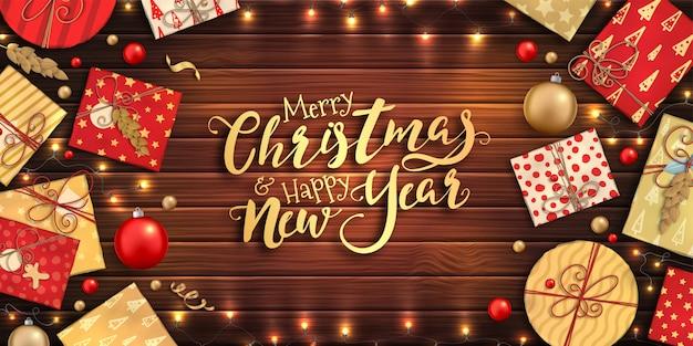 Feliz natal e feliz ano novo pôster com enfeites coloridos, caixas de presente vermelhas e douradas, guirlandas em fundo de madeira