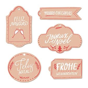 Feliz natal em diferentes idiomas. conjunto de etiquetas de presente de papel. feliz navidad em espanhol, frohe weihnachten em alemão, joyeux noel em francês. letras de mão vintage.