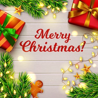 Feliz natal! mesa de madeira decorada com presentes, galhos de árvores de natal, boneco de gengibre e fio de luzes. vista do topo.