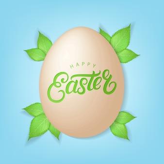 Feliz páscoa fundo. mão escrita letras no ovo realista com folhas verdes da primavera.