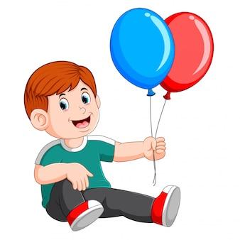 Feliz um menino sentado e carregando dois balões