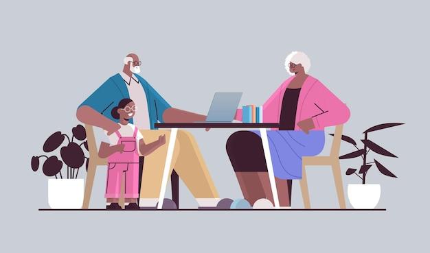 Felizes avós afro-americanos com a neta usando laptop para comunicação on-line de rede de mídia social
