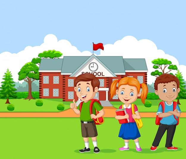Felizes crianças em idade escolar em frente à escola