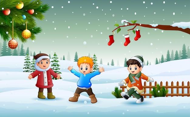 Felizes crianças vestindo um inverno chlotes brincando na neve no dia de natal