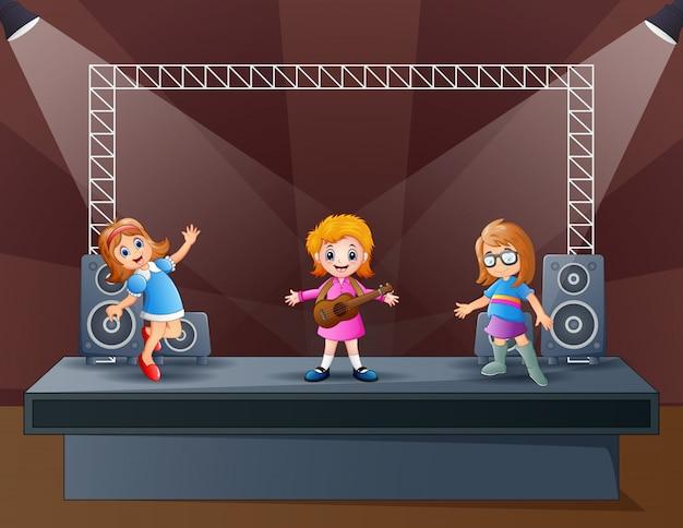Felizes três meninas realizando no palco Vetor Premium