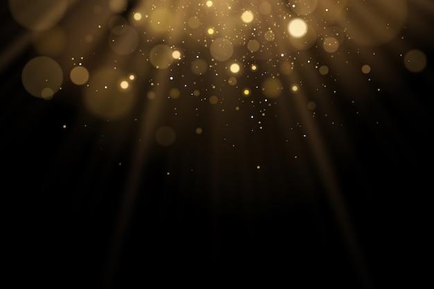 Flash de luz dourada com brilhos bokeh em um fundo preto. raios de luz com glitter.