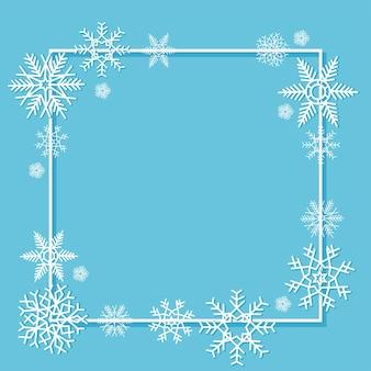 Flocos de neve brancos em uma moldura sobre um fundo azul. um cartão postal com um lugar para texto.