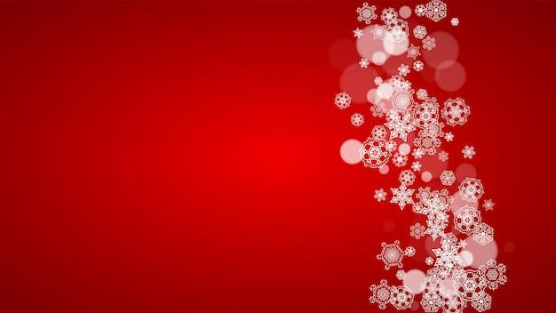 Flocos de neve de natal em fundo vermelho. cores do papai noel. quadro horizontal de flocos de neve de natal para banners de férias, cartões, vendas, ofertas especiais. queda de neve com bokeh para a celebração da festa