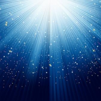 Flocos de neve e estrelas na luz azul.