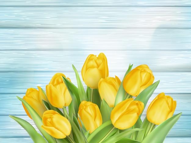 Flores tulipas amarelas em pranchas de madeira.