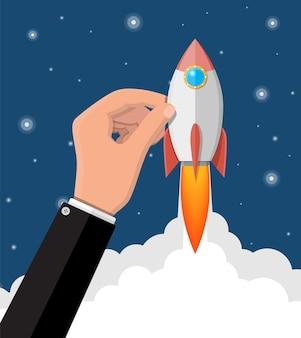Foguete de desenho animado na mão do empresário. a nave espacial decola. conceito de inicialização de negócios. ilustração em estilo simples