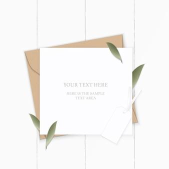 Folha de natureza plana lay top view elegante composição branca carta papel kraft envelope e tag em fundo de madeira.