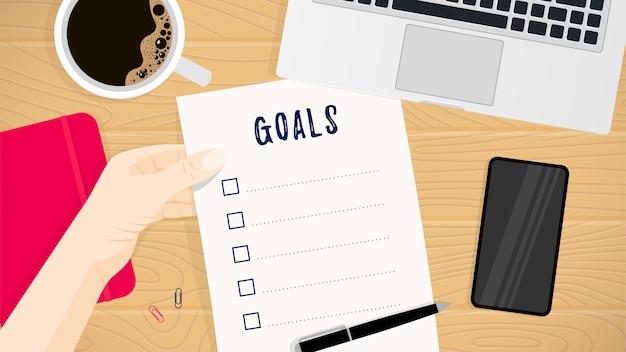 Folha de papel com objetivos listar modelo na mão, café, caderno, laptop, smartphone, caneta na mesa de madeira, vista superior.