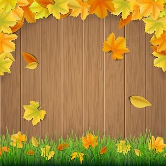 Folhas de outono, tábuas de madeira e grama verde