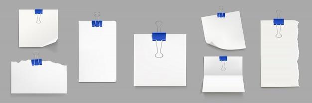 Folhas de papel branco com clipes de fichário azuis