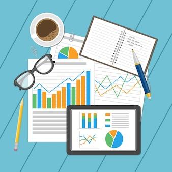 Folhas de papel e tablet com ilustração de tabelas e gráficos analíticos