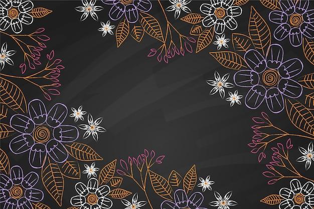 Folhas e flores douradas sobre fundo de quadro-negro