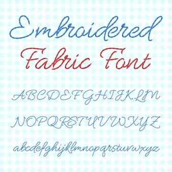 Fonte de tecido bordado com letras caligráficas.