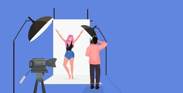 Fotógrafo profissional usando o homem da câmera tiro modelo sexy mulher bonita levantando as mãos posando no estúdio de fotografia moderno horizontal comprimento total