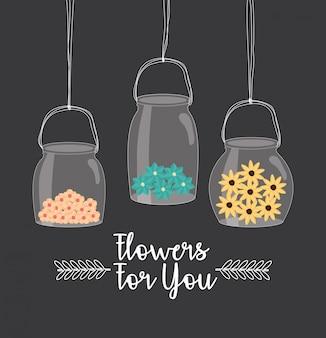Frascos de pedreiro com flores penduradas