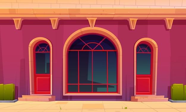 Frente da loja com portas de vidro e janela em arco na fachada de prédio antigo