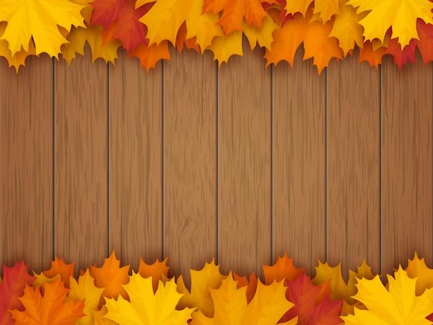Fronteira de folhas de bordo caídas no fundo de uma superfície de mesa de madeira vintage.