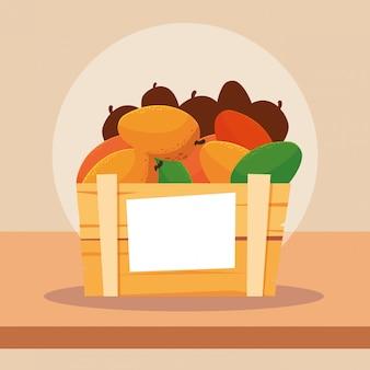 Frutas frescas de mangas em caixa de madeira