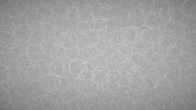 Fundo abstrato de contornos dispostos aleatoriamente de círculos em cores cinza.