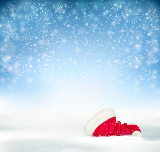 Fundo azul do feriado do natal com chapéu de papai noel, neve e flocos de neve.