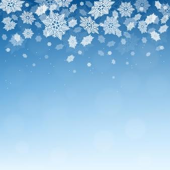 Fundo azul do inverno do natal com flocos de neve caindo.