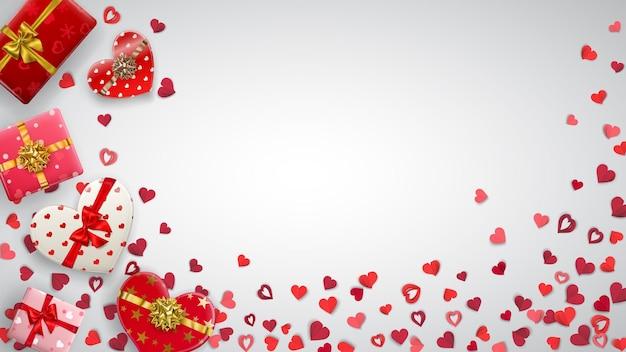 Fundo com pequenos corações vermelhos e caixas de presente coloridas com fitas, laços e vários padrões